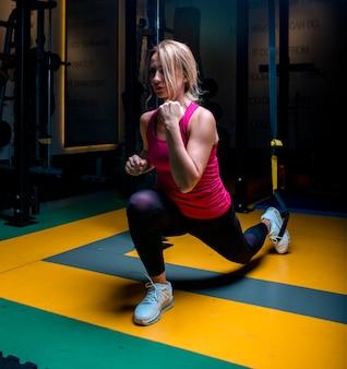 Mujer en rosa haciendo actividades de calentamiento y estiramiento en un gimnasio.