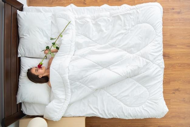 La mujer con una rosa tendida en la cama. vista desde arriba