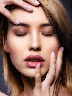 Mujer con rostro de belleza y piel limpia. mujer rubia sexy. atractiva modelo rubia de ojos azules. modelo de moda con un maquillaje ahumado. closeup retrato de una mujer bonita. peinado corto creativo.