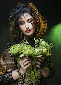 Mujer con rostro brigt sosteniendo grandes flores verdes