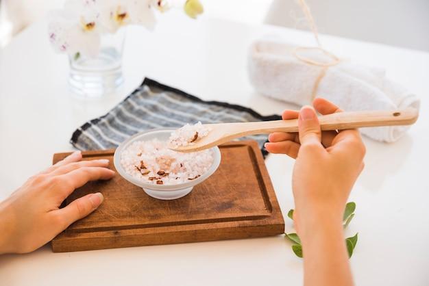 Mujer sin rostro con cuchara y sal rosada en un tazón sobre tabla para cortar