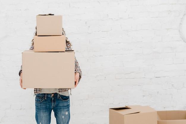 Mujer sin rostro llevando cajas