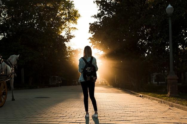 Mujer sin rostro en el parque en la puesta del sol