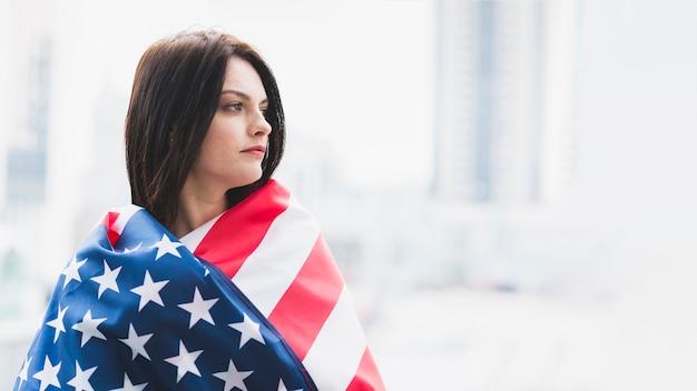 Mujer de rostro sombrío envuelta en bandera americana.