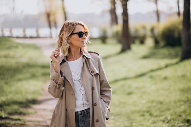 Mujer rubia en abrigo afuera en el parque