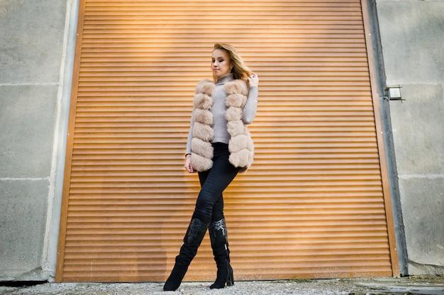 Mujer rubia en abrigo de pieles contra la pared con persianas.