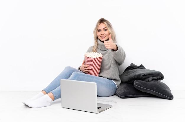 Mujer rubia adolescente comiendo palomitas de maíz mientras mira una película en la computadora portátil con los pulgares hacia arriba porque algo bueno ha sucedido