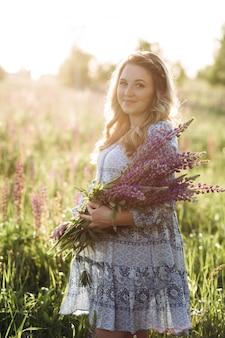 La mujer rubia adorable en vestido azul camina a través del campo de las flores violetas de la lavanda