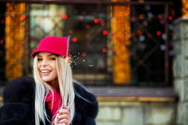 Mujer rubia alegre celebrando el año nuevo con luces de bengala en el fondo bokeh. espacio para texto