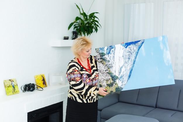 Una mujer rubia anciana feliz sostiene un gran lienzo de fotos de pared en casa