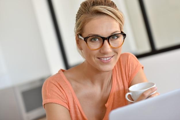 Mujer rubia con anteojos trabajando desde casa con laptop