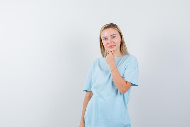Mujer rubia apoyando la barbilla en el puño en camiseta azul y mirando feliz