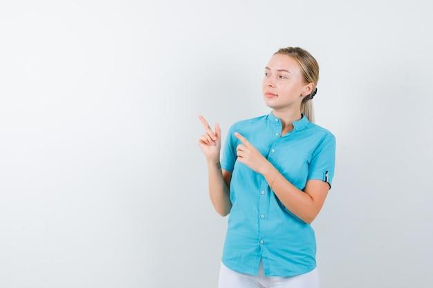 Mujer rubia apuntando a la esquina superior izquierda en blusa azul aislada