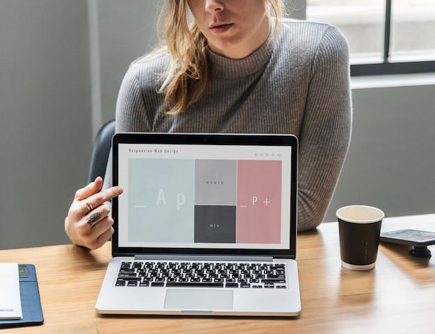 Mujer rubia apuntando a la pantalla de un portátil