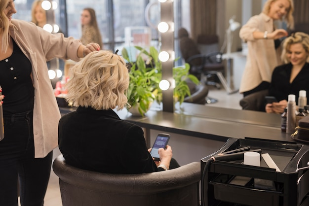 Mujer rubia arreglándose el pelo