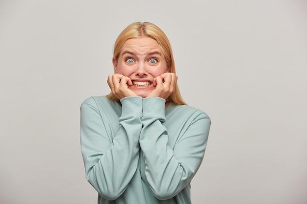 Mujer rubia asustada se ve asustada, asustada, castañeteo de dientes con miedo, ve algo aterrador en el frente