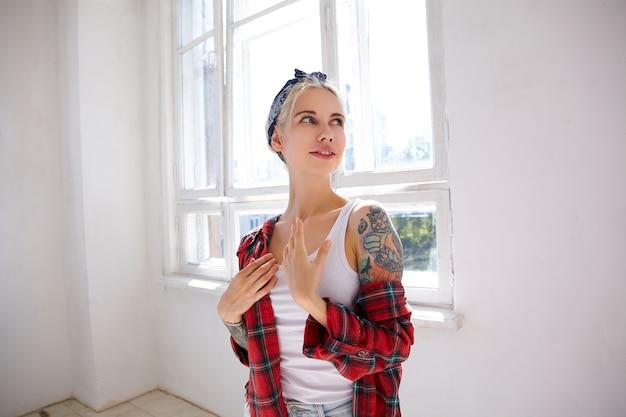 Mujer rubia atractiva joven positiva con tatuajes vestida con camisa a cuadros manteniendo las palmas en el pecho mientras mira con alegría a un lado, posando frente a una ventana grande