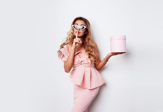 Mujer rubia atractiva que sostiene la caja de regalo y que presenta en vestido rosado sobre la pared blanca. concepto de compras y celebración. gafas de sol de moda.