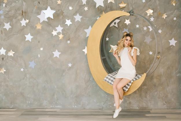 Mujer rubia atractiva soñadora cabalgando sobre la luna.