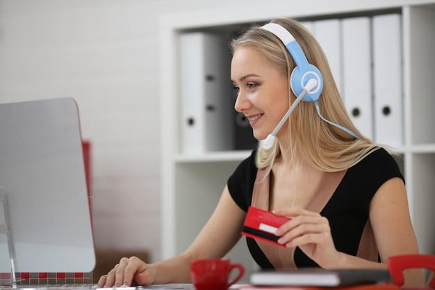 Mujer rubia en auriculares con micrófono en la cabeza con servicio de soporte de tarjeta de crédito