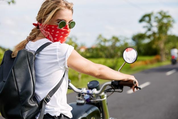 Mujer rubia con bandana en moto
