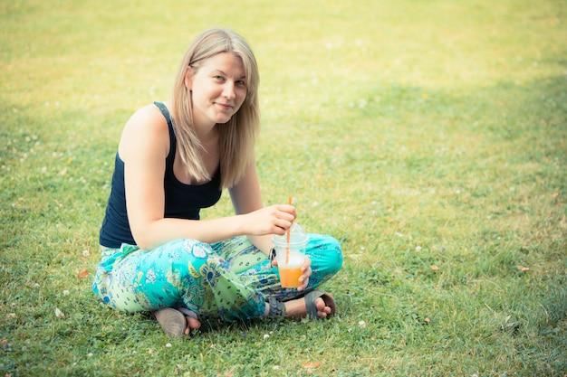 Mujer rubia bebiendo jugo de frutas en el parque