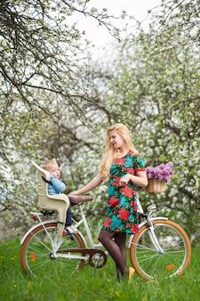 Mujer rubia con bicicleta de ciudad con bebé en silla de bicicleta