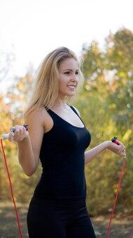 Mujer rubia bien formada en ropa deportiva de pie con una cuerda en sus manos en un parque