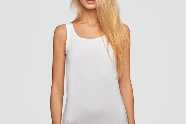 Mujer rubia en bikini blanco o camiseta con espacio en blanco para su anuncio, muestra cuerpo en forma