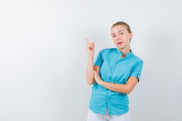 Mujer rubia en blusa azul apuntando a la esquina superior izquierda aislada