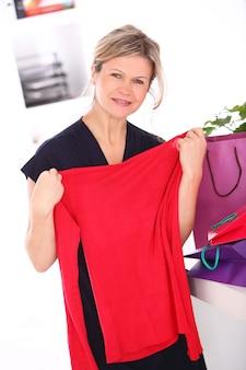 Mujer rubia con una blusa roja en sus manos