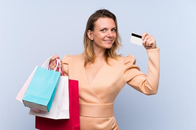 Mujer rubia con bolsas de compras y una tarjeta de crédito
