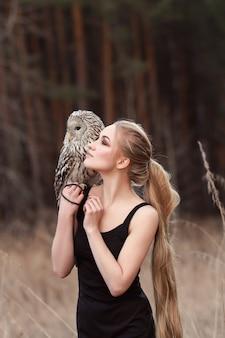 Mujer rubia con un búho en sus manos camina en el bosque en otoño y primavera