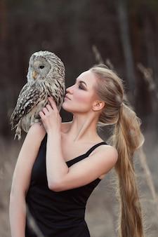 Mujer rubia con un búho en sus manos camina en el bosque en otoño y primavera.