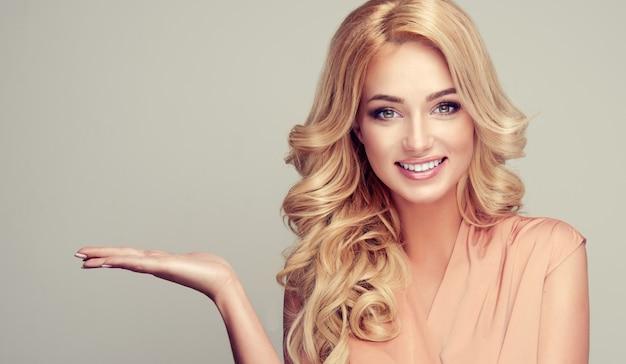 Mujer rubia con cabello rizado muestra tu producto