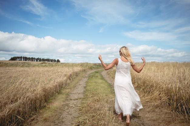 Mujer rubia caminando por el sendero en el campo