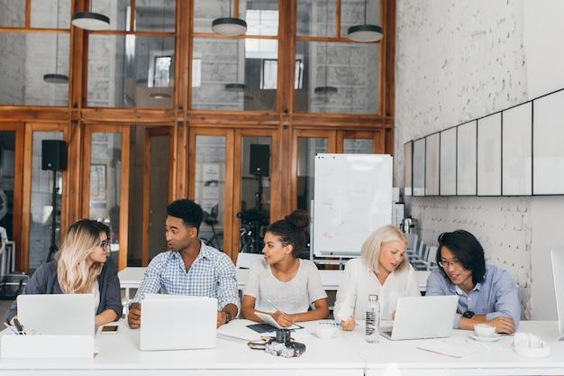 Mujer rubia en camisa blanca hablando con un amigo asiático y tomando café cerca de la computadora portátil con rotafolio. diseñadores web independientes que trabajan juntos en una sala de conferencias y usan computadoras.