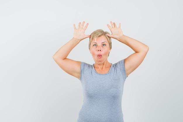 Mujer rubia en camiseta azul claro levantando sus palmas en señal de rendición y mirando sorprendido, vista frontal.