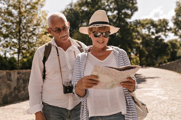 Mujer rubia en camiseta blanca, blusa azul, gafas de sol y sombrero sonriendo y mirando el mapa. señora camina con hombre bigotudo en camisa con cámara al aire libre.