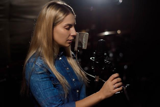 Mujer rubia cantando en un estudio de grabación