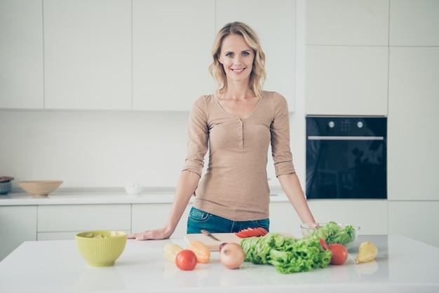 Mujer rubia en casa en la cocina con verduras