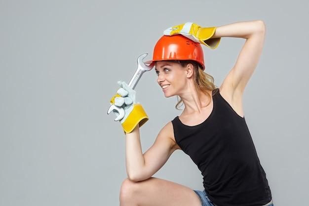 Mujer rubia. en un casco protector y guantes, sosteniendo una llave grande.