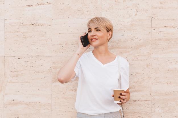 Mujer rubia caucásica con camiseta blanca hablando por teléfono celular, mientras está de pie contra la pared beige al aire libre en verano y tomando café de una taza de papel