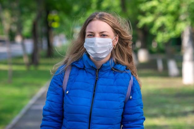 Mujer rubia caucásica en máscara protectora y guantes está caminando por la calle vacía. comportamiento seguro durante una pandemia
