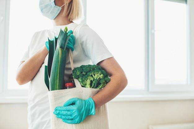 Mujer rubia caucásica está posando con una bolsa de productos con una máscara y guantes