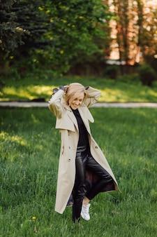 Mujer rubia caucásica wearind trinchera sonríe felizmente en un día soleado de primavera afuera caminando en el parque