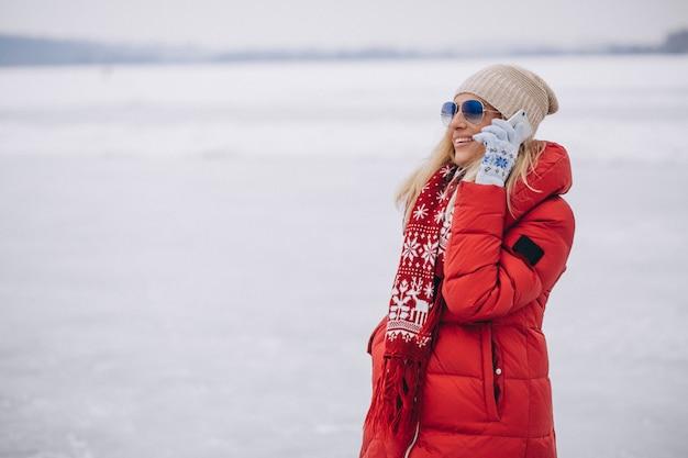 Mujer rubia en chaqueta roja afuera en invierno