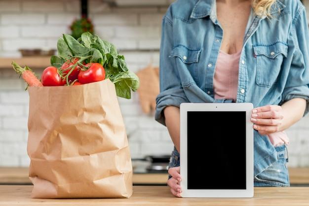 Mujer rubia en la cocina con una tablet