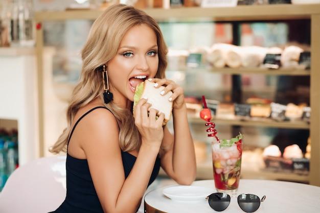 Mujer rubia comiendo delicioso sandwich en café