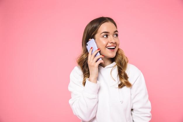 Mujer rubia complacida con ropa casual hablando por teléfono inteligente y mirando a otro lado sobre la pared rosa